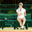 Female tennis player rests at the bench — Stock Photo #13346765