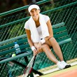 Stock Photo: Young female tennis player rests at bench