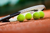 Close up view of tennis racquet and balls — Stock Photo