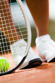 Legs of sportswoman near the tennis racket and balls — Stock Photo
