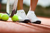 Jambes d'athlète près de la raquette de tennis et balles — Photo