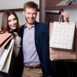 Cheerful couple show their purchases — Stock Photo #13538535