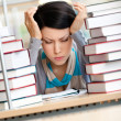 Tired beautiful woman surrounded with books — Stock Photo