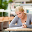 Female student drilling at the desk — Stock Photo