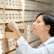 Young woman searches something in card catalog — Stock Photo