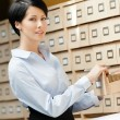Beautiful woman seeks something in card catalog — Stock Photo