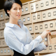Stock Photo: Beautiful woman seeks something in card catalog