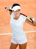 Woman keeps tennis racquet and ball on her shoulders — Stock Photo