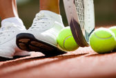Legs of athletic girl near the tennis racket and balls — Stock Photo
