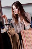 Tala i telefon och köpa kläder i butiken — Stockfoto