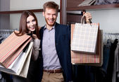 Cheerful couple show their purchases — Stock Photo