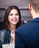 Smiling girl talks to shop assistant — Stock Photo