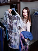 Hesitating about clothes at the store — Stock Photo