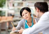 Mooie vrouw communiceert met jonge man in de bibliotheek — Stockfoto