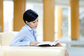 Business woman rests at the sofa with book — Stock Photo