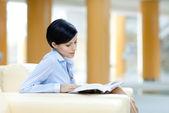 Obchodní žena odpočívá na pohovce s knihou — Stock fotografie
