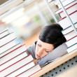 Female student sleeping at the desk with piles of books - Stock Photo