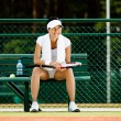Successful female tennis player rests at the bench — Stock Photo #13693135