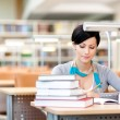 Young female studies with piles of books — Stock Photo