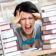 Tired pretty woman surrounded with books — Stock Photo
