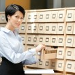 Young woman looks for something in card catalog — Stock Photo