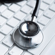 Close up view of stethoscope on laptop keyboard — Stock Photo #13696834