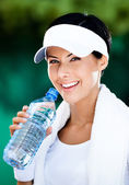 Smiley sporty woman with bottle of water — Stock Photo