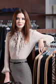 Beautiful woman and wide choice of clothes — Stock Photo