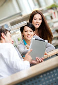 Young man at the library shows tablet to two women — Stock Photo