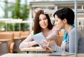 Twee meisjes spreken vergadering aan de tafel — Stockfoto