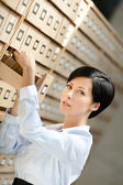 Young woman seeks something in card catalog — Stock Photo