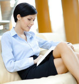 Business woman on the sofa with book — Stock Photo
