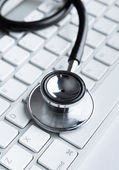 Close up view of stethoscope on laptop keyboard — Foto Stock