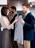 Consulting with girlfriend while selecting a shirt — Zdjęcie stockowe