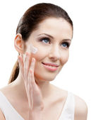 Woman applying cream on her face — Stock Photo