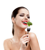 Pretty girl eating broccoli on fork — Stock Photo