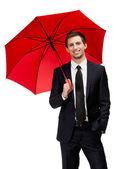 Businessman holding umbrella overhead — Stock Photo