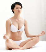 Woman meditates sitting on the bedstead — Stock Photo