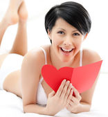 Woman in underwear hands a post card — Stock Photo