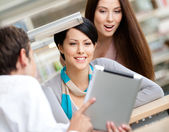 Man at the library shows pad to two women — Stock Photo