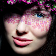 Close up of blue-eyed woman with flowers — Stock Photo