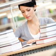 Woman surrounded with piles of books reads sitting at the desk at the library — Stock Photo #14049583