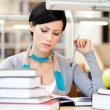 Pretty woman reads sitting at the desk — Stock Photo