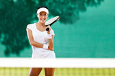 Beautiful sportswoman with racquet at the tennis court — Stock Photo