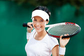 Hübsche sportlerin mit schläger auf dem tennisplatz — Stockfoto