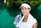 Athletic woman with bottle of water — Stock Photo