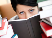 Young female looks out over the book — Stock Photo