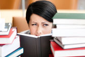 Pretty female student looks out over the book — Stock Photo