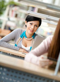Smiley woman sits at the desk — Stock Photo