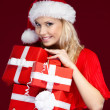 Young woman in Christmas cap holds a set of presents — Stock Photo